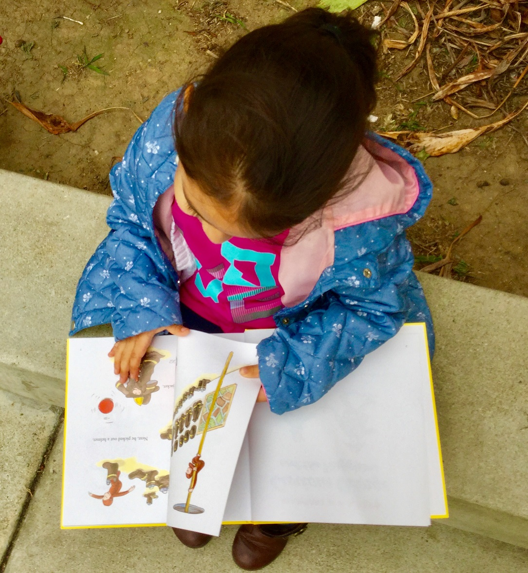 Kindergartner enjoying her book from Reading to Kids