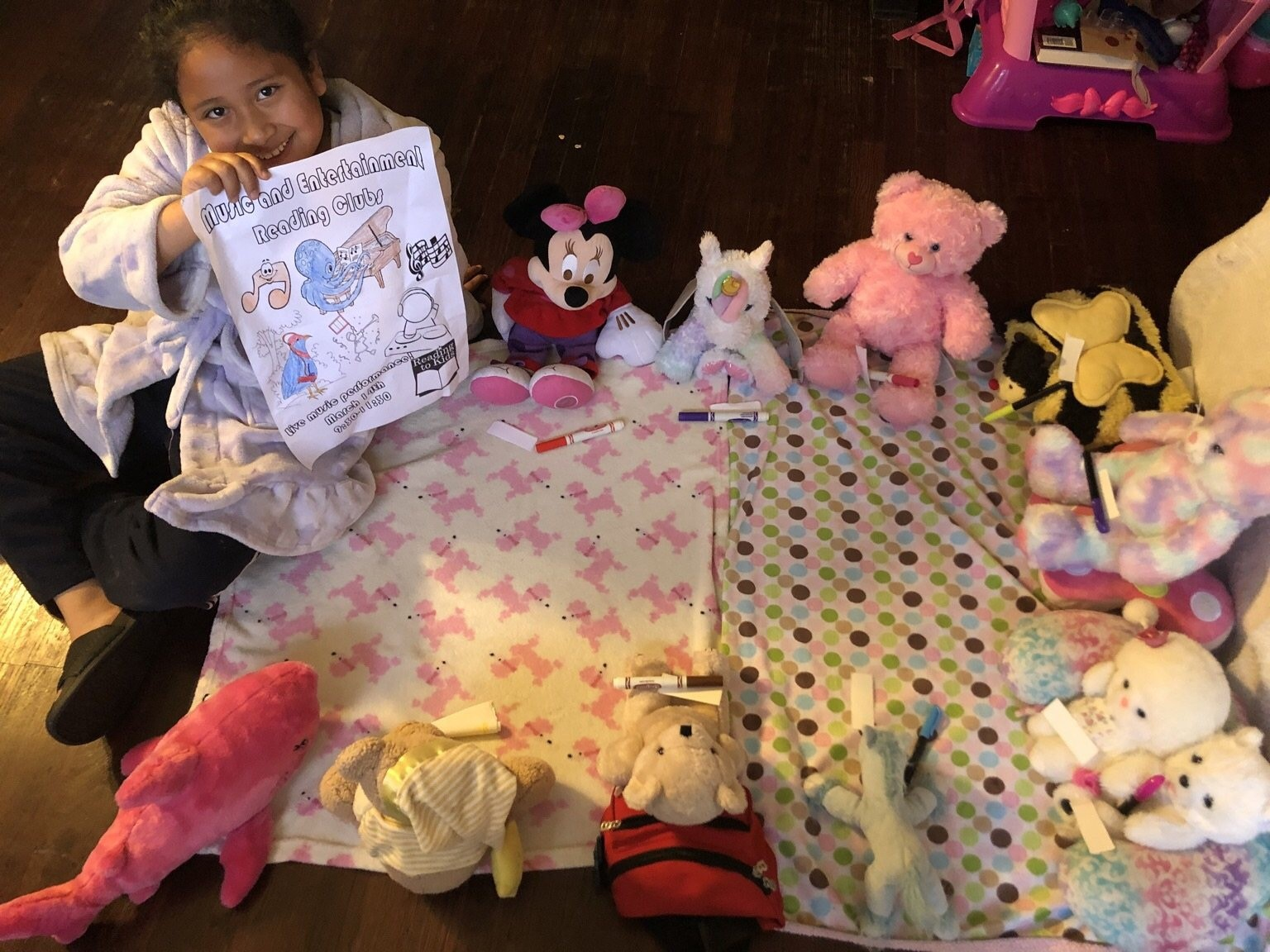 A girl shows her craft she created while holding a Reading to Kids reading club at home