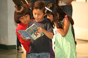 Three kids with a prize book