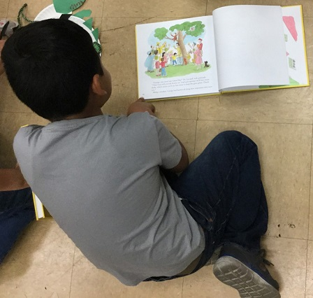 A Politi 3rd grader enjoys a book he received from Reading to Kids